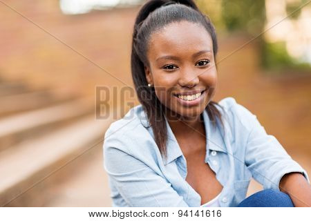 portrait of african american female university student sitting outdoors