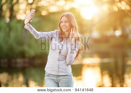 Young girl holding a smartphone digital camera her hands and taking selfie self portrait  herself outdoors enjoying nature  Urban Model woman in Casual jeans in sun light  Backlit Warm Color Tones