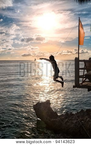 Silhouettes of child jumping in sea over sunset