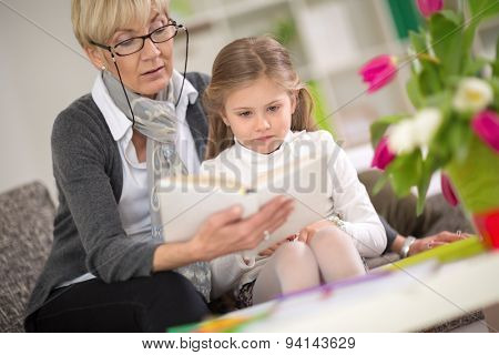 girl interested looks at the book which her grandmother read