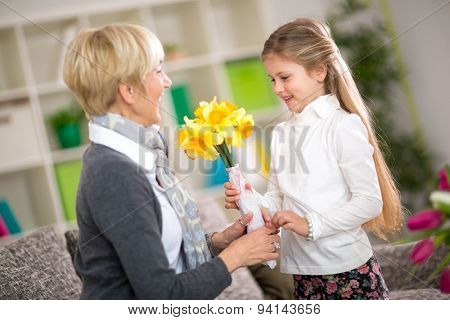 Granddaughter bringing yellow flowers to her grandmother, grandmother day
