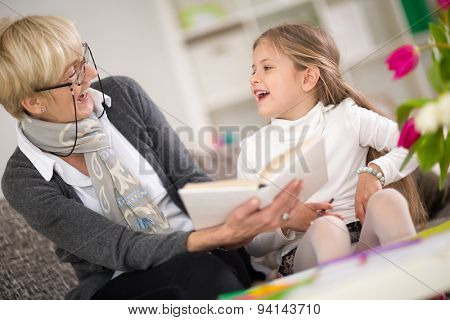 little girl with grandma reading interested book