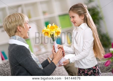 Happy cute girl giving flower her grandma on grandmother day