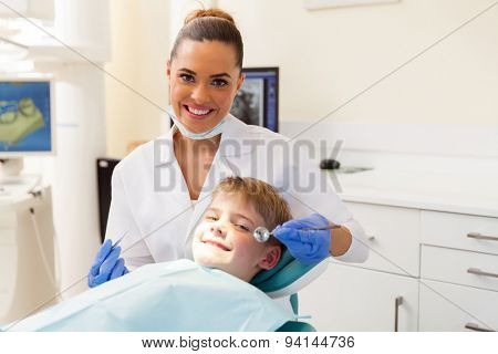 happy dentist consulting little patient in office