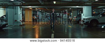 A Tattooed Man Is Walking On The Parking Lot