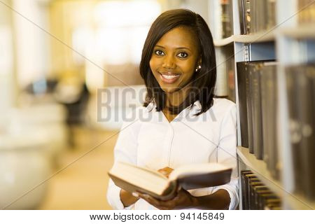 young african college student reading a book in library
