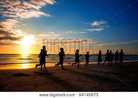 group of young people runs at the beach on beautiful summer