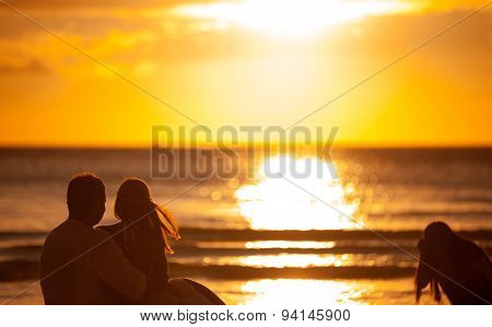 newlyweds with a photographer on the beach, taking romantic images for remember
