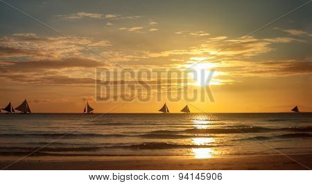 Beach sunset scene with small sailboat