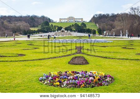 Flowerbed, Tourists, Neptune Fountain and Gloriette at Schonbrunn, Vienna, Austria