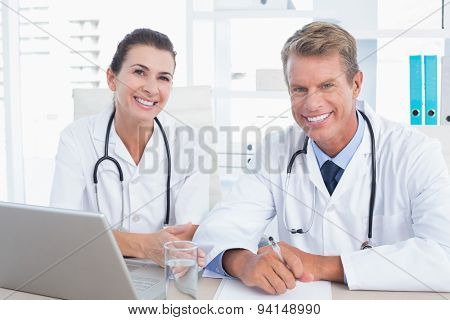 Smiling doctors looking at camera in medical office