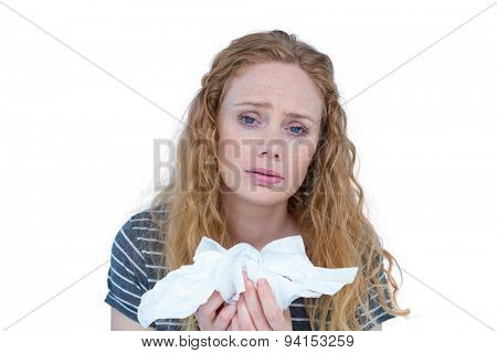 Sick blonde woman holding paper tissue on white background