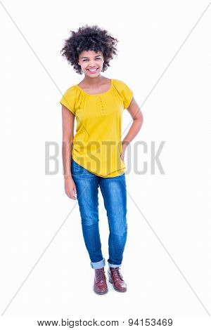 Pretty hipster with hand on hips smiling at camera on white background