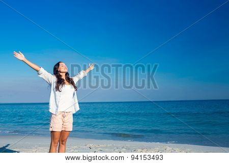 Happy woman with eyes closed at the beach on a sunny day
