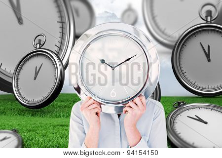 Businesswoman hiding face with clock against grey sky over field