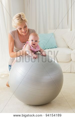 Happy mother with her baby girl in the exercice ball at home in the living room