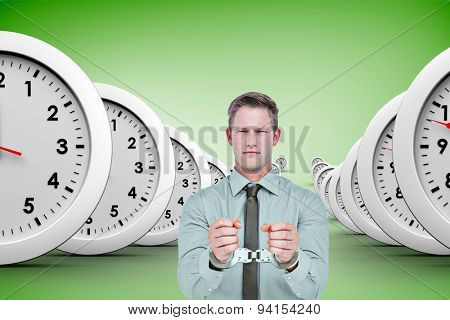 Handsome businessman wearing handcuffs against green vignette
