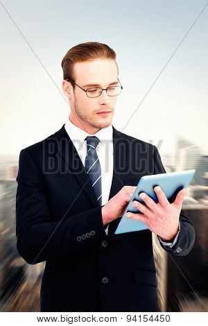 Unsmiling businessman using tablet pc against new york skyline