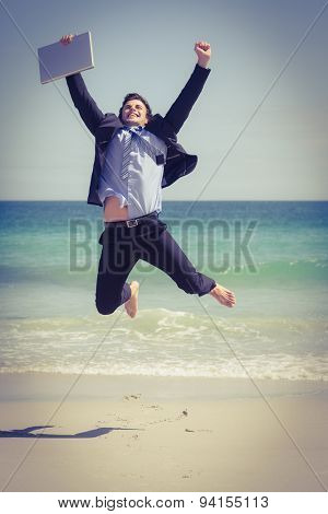 Excited businessman wearing a suit is jumping on the beach