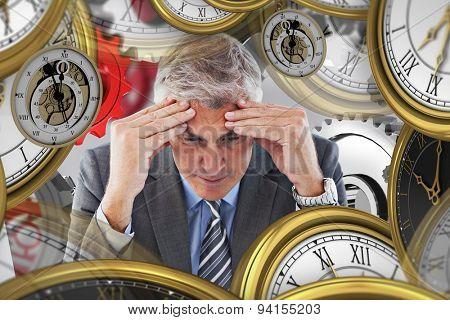 Worried businessman at desk against grey vignette