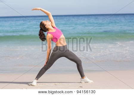 Fit woman stretching her back at the beach
