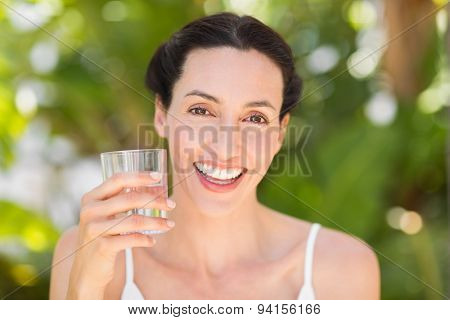woman in white having a glass of water on a sunny day