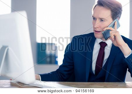 Businessman working on his computer and having a phone call in his office