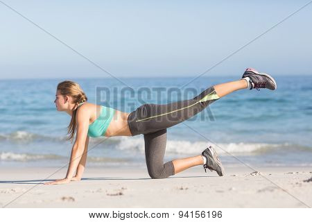 Fit woman stretching her leg at the beach