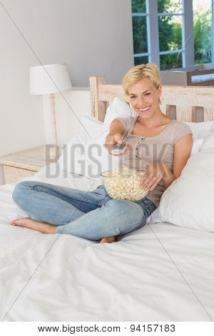 Smiling blonde woman watching TV and eating pop corn at home in bedroom