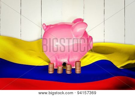 Coins and piggy bank against wooden planks