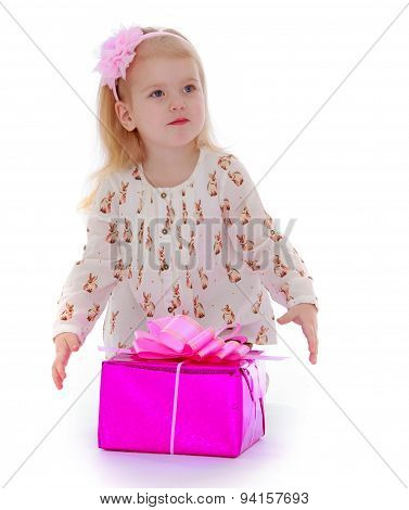 Cute little girl about gift boxes