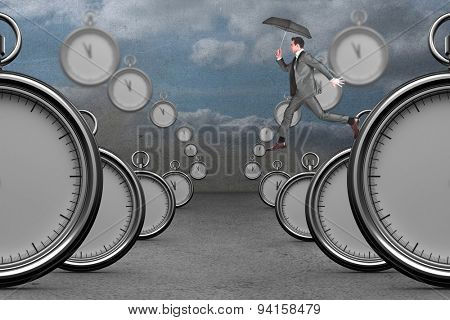 Businessman jumping holding an umbrella against clouds in a room