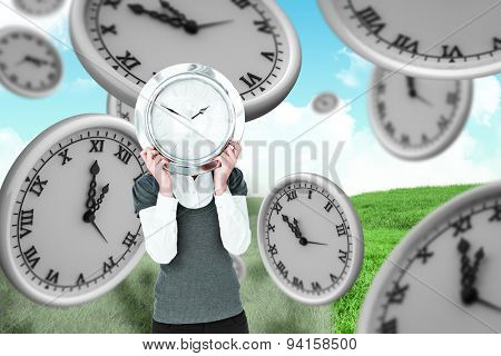 Woman holding clock in front of her head against green field under blue sky