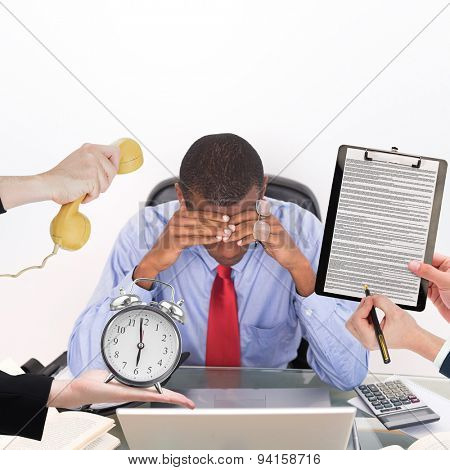 hand holding phone against frustrated afro businessman with head in hands at desk