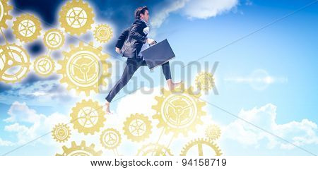 Leaping businessman against blue sky