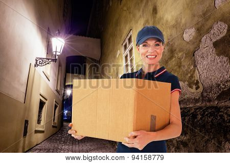 Happy delivery woman holding cardboard box against building by night