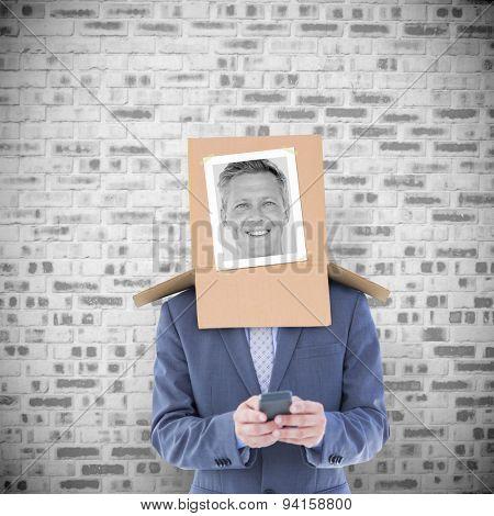 Businessman with photo box on head against grey brick wall