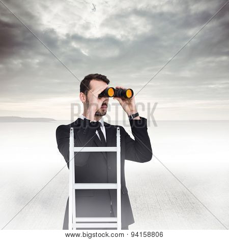 Businessman looking on a ladder against grey sky