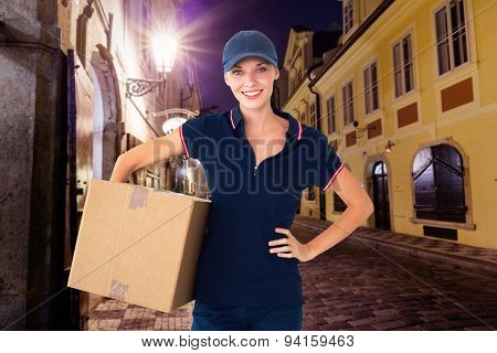 Happy delivery woman holding cardboard box against city by night