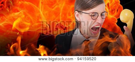 Geeky businessman shouting at retro phone against fire
