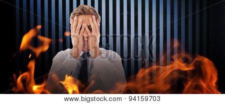 Businessman with a headache against dark grey room
