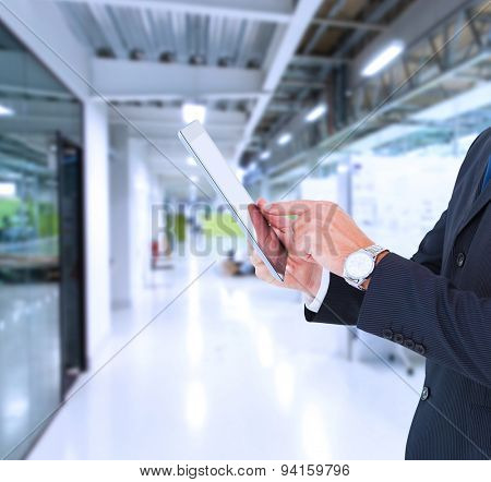 Businessman in suit using digital tablet against college hallway