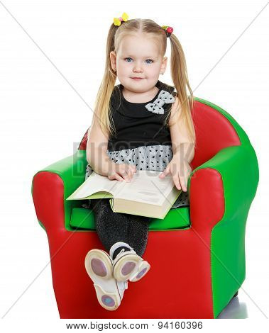 Blonde little girl reading a book sitting on the chair
