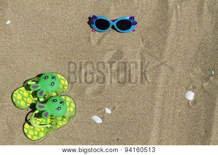 Children's slippers beach bunny on green sand and sunglasses