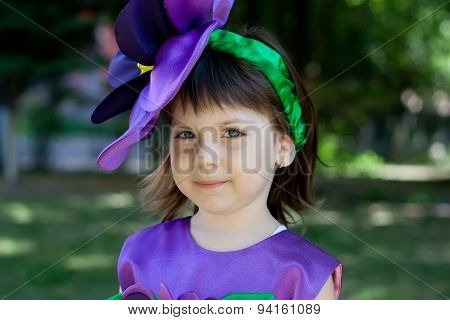 The Little Girl In A Suit Of Violet Flower Is Smiling On The Background Of The Park. Close-up Portra