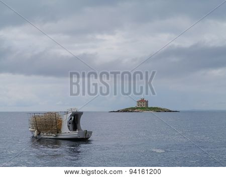 The island Trstenik with a fishing vessel