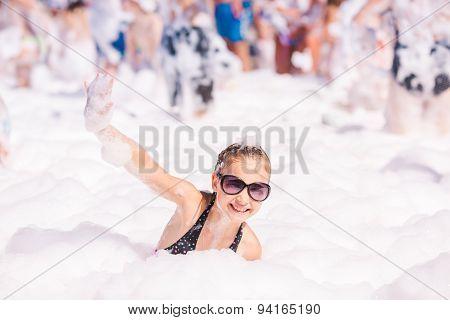 Cute Little Girl Having Fun At Foam Party.
