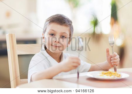Little boy eats his breatkfast on the kithen