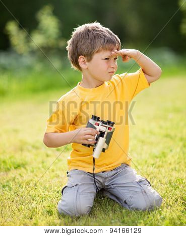 Portrait of little boy with binoculars on the grass