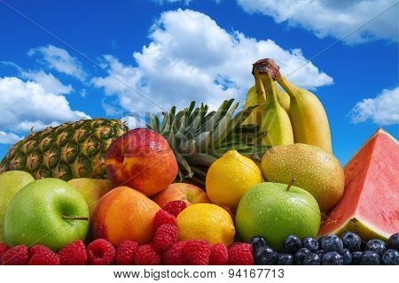 Assortment of exotic fruits and blue sky with puffy white clouds